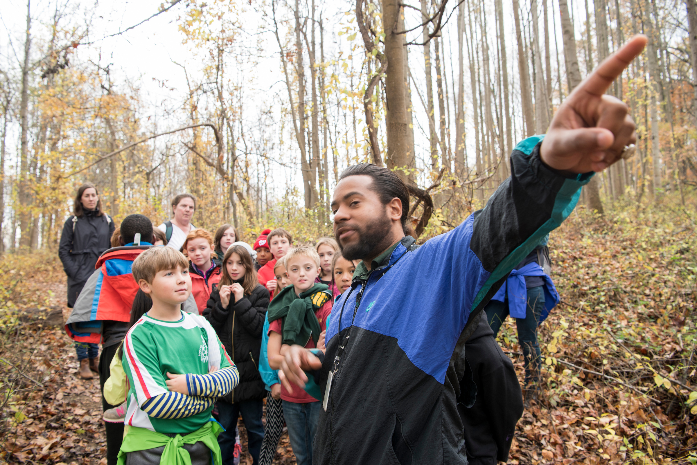 Students listening to an expert in the woods on a field trip.
