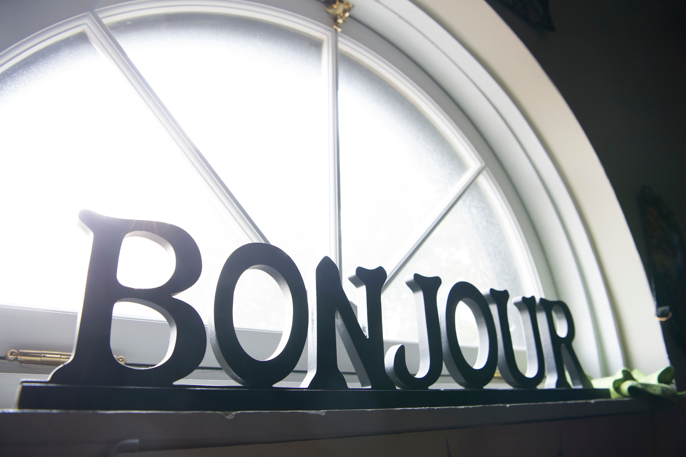 "A picture of a piece of art in a classroom window that says ""Bonjour."""