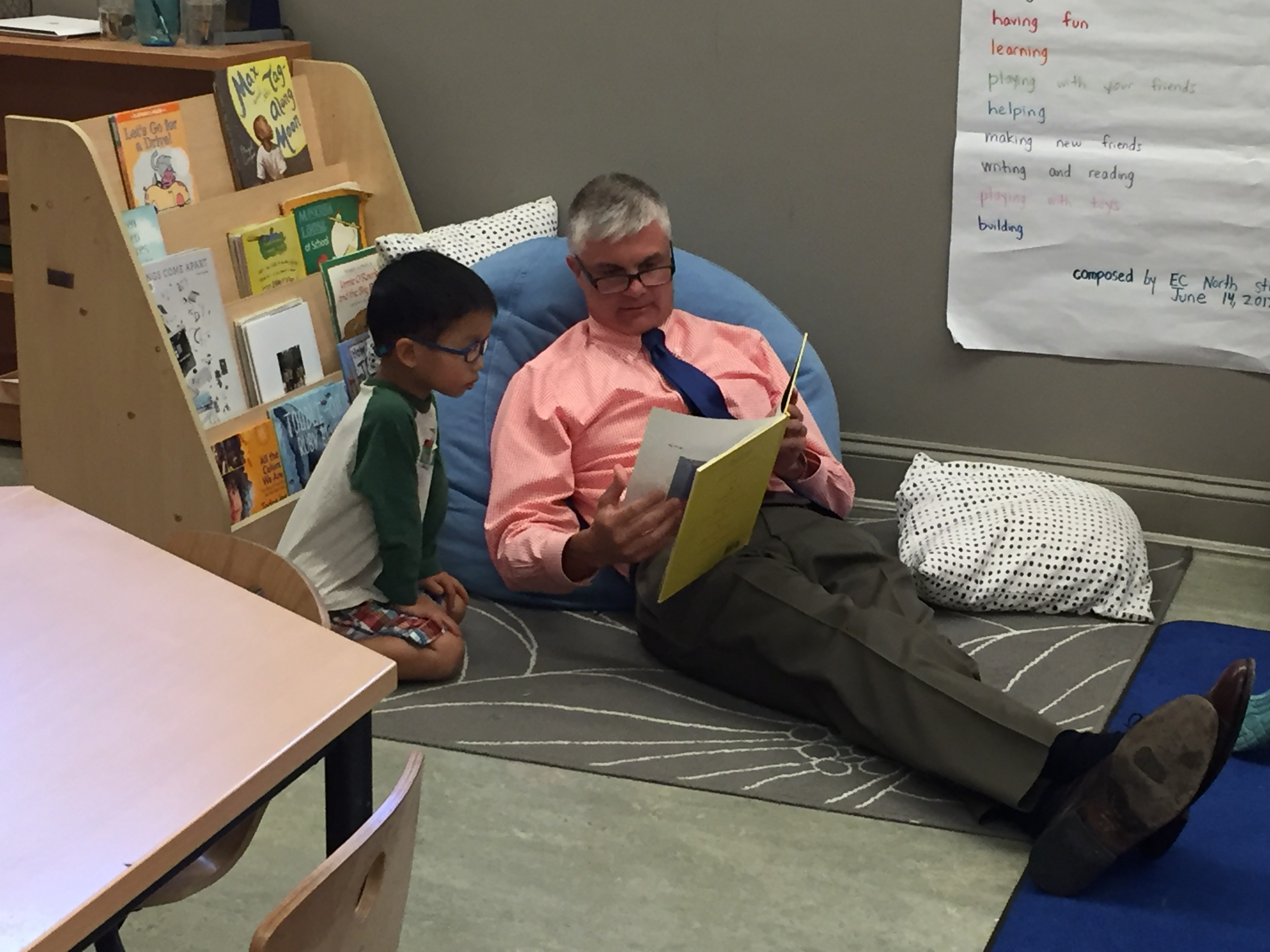 Head of School, Jason Gray, reading to an Early Childhood student on a beanbag chair.
